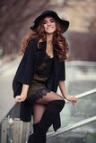 Beautiful young woman in fashion black coat, hat,  lace dress an. D boots with high heels smilling outside. Vogue style Royalty Free Stock Photo
