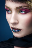 Beautiful young woman with fashion makeup isolated on blue Stock Photography