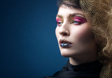 Beautiful young woman with fashion makeup isolated on blue Royalty Free Stock Photo