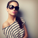 Beautiful young woman in fashion sunglasses posing and looking. Royalty Free Stock Photos