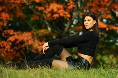 Beautiful young woman in fashionable black clothes sitting in the park. Royalty Free Stock Photography