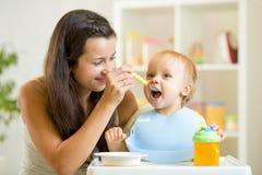 Beautiful young woman feeds child boy Stock Image