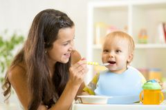 Beautiful young woman feeds her son baby stock photo