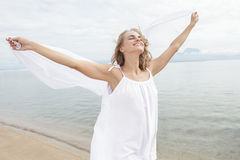 Beautiful young woman feeling happy with white scarf. Portrait of beautiful young woman feeling happy with white scarf on the beach Stock Photo