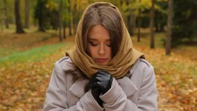 Beautiful young woman feels cold and ready to cry out in an autumn park. Attractive girl stands in a picturesque autumn park, dressed in grey coat, black stock video footage