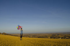Beautiful young woman in the field holding balloons. Beautiful young woman in the yeloow field holding balloons Royalty Free Stock Photo