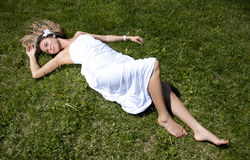 Beautiful young woman on field in summer. Portrait of the young woman lying on a grass in summer Royalty Free Stock Photo