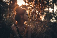 Beautiful young woman on a field at sunset Stock Image