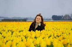 Beautiful young woman on field of yellow tulips. Beautiful young woman on the field of yellow tulips, the Netherlands Stock Photos