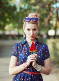 Beautiful young woman in fifties style with candy. Outdoor Stock Photos