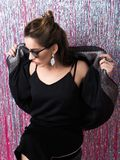 Sexually dressed girl in earings and sunglasses. Beautiful young woman in fine earings and sunglasses wearing a black skirt, sexy top and a fashionable jacket Stock Photography