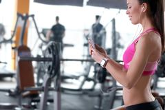 Beautiful young woman with fitness tracker listening to music. In gym Stock Photography