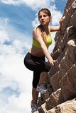 Beautiful young woman in fitwear climbing Stock Photography