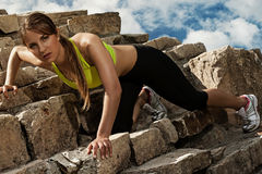 Beautiful young woman in fitwear climbing Stock Photo