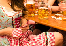Beautiful young woman fixing her Dirndl at Munich Oktoberfest Royalty Free Stock Image