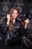 Beautiful young woman fixing her makeup Royalty Free Stock Photo