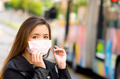 Beautiful young woman fixing her protective mask on the street in the city with air pollution with a blurred bus behind Royalty Free Stock Photo
