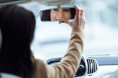 Beautiful young woman fixing rear view mirror of the car. Royalty Free Stock Photo