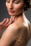 Beautiful young woman with flawless complexion holding necklance Royalty Free Stock Image