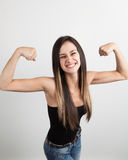 Beautiful young woman flexing her biceps Stock Photography