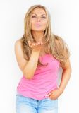 Beautiful young woman flirting and blowing a kiss Royalty Free Stock Photography