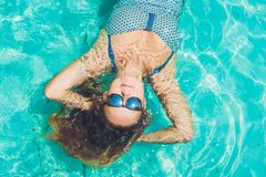 Beautiful young woman floating in pool relaxing Top view. Holida Royalty Free Stock Photos