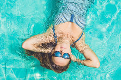 Beautiful young woman floating in pool relaxing Top view. Holiday concept.  royalty free stock photo