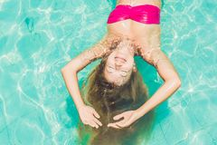 Beautiful young woman floating in pool relaxing Top view. Holida Stock Images