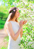 Beautiful young woman with floral headband enjoys spring flowers Stock Images