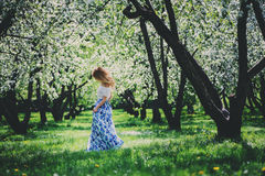 Beautiful young woman in floral maxi skirt walking in spring Royalty Free Stock Photo