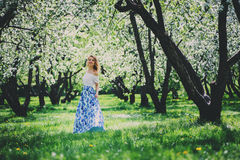 Beautiful young woman in floral maxi skirt walking in spring Royalty Free Stock Image