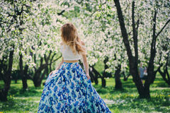 Beautiful young woman in floral maxi skirt walking in spring Stock Photography