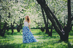Beautiful young woman in floral maxi skirt walking in spring Stock Images