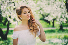 Beautiful young woman in floral maxi skirt walking in spring Stock Image