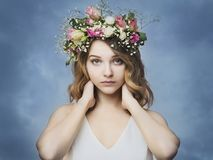 Beautiful young woman in a floral wreath of roses Stock Image
