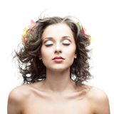 Beautiful young woman with flower in blowing hair. Standing with closed eyes isolated on white Stock Photos
