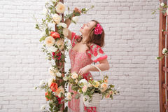 Beautiful young woman with flower in hair keeps bascket full of flowers. stock image
