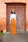 Beautiful young woman with flower wreath on her head near the wooden door Royalty Free Stock Image