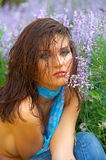 Beautiful young woman between flowers Stock Images