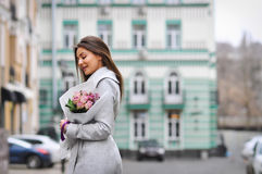 Beautiful young woman with flowers bouquet at city street. Spring portrait of pretty female Stock Image