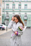 Beautiful young woman with flowers bouquet at city street. Spring portrait of pretty female Stock Photos