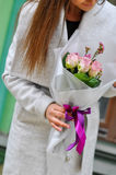 Beautiful young woman with flowers bouquet at city street. Spring portrait of pretty female Royalty Free Stock Image