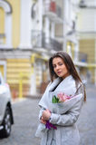 Beautiful young woman with flowers bouquet at city street. Spring portrait of pretty female Stock Images