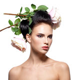 Beautiful young woman with flowers in hair. Stock Photos