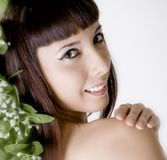 Beautiful Young Woman With Flowers In Her Hair. Young brunette woman with flowers in her hair, focus on face Stock Photos
