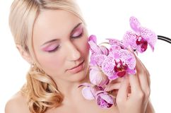 Beautiful young woman with flowers of orchid Royalty Free Stock Images