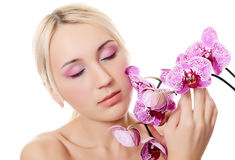 Beautiful young woman with flowers of orchid Royalty Free Stock Photos