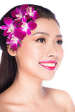 The beautiful young woman with flowers of orchid Stock Photos