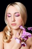 The beautiful young woman with flowers of orchid Royalty Free Stock Photo
