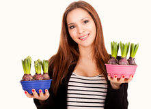 Beautiful young woman with flowers in pots Stock Image